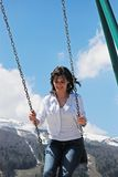 Swing. Young woman swinging with snow mountain in background Stock Image