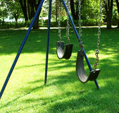 Swing. Black swing hanging in garden Royalty Free Stock Images