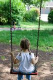 On the swing. Little girl on the swing Stock Images