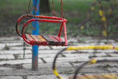 Swing. Old red swing on a playground Stock Photos