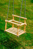 Swing. Wooden swing on green background Stock Photos