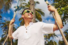 Swing on the beach. Young man on the swing under palm tree Royalty Free Stock Images