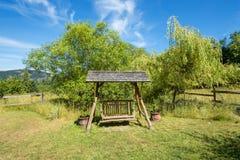 Swing bench in a lush garden Stock Photos