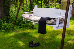 Swing bench in lush garden Stock Image