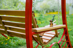 Swing bench near children house in garden. Stock Photos