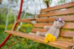 Swing bench near children house in garden. Stock Photography