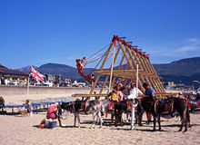 Swing boats and donkeys on Barmouth beach. Stock Images