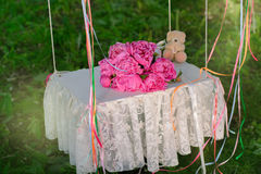 Swing with a bouquet of flowers. And a small teddy bear Royalty Free Stock Photos