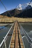 Swing Bridge crossing to snow capped Mountains Royalty Free Stock Image