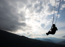 Swing at the Casa del Arbol in Banos, Ecuador. Silhouette of happy young man on a swing with a fantastic mountain view at the Casa del Arbol, Ecuador Royalty Free Stock Images