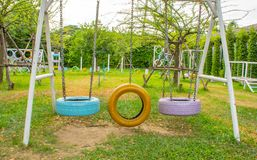 Swing chairs made from old tires for children in park. stock photography