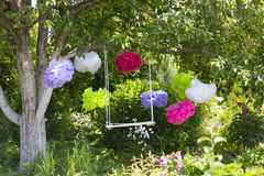 The swing and colorful paper flowers hanging on the tree Royalty Free Stock Image