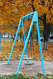 Swing. Desert park full of golden foliage, lonely blue iron fast childish swing isolated royalty free stock photos