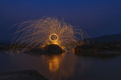 Swing fire. Rotating lights,Color of fire swing on the stone at river in night time royalty free stock image