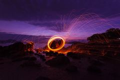 Swing fire Swirl steel wool light photography over the stone with reflex in the water Beautiful light in the sunrise or sunset. Time, long exposure speed motion stock images