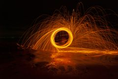 Swing fire Swirl steel wool light photography over the stone with reflex in the water long exposure speed motion style.  royalty free stock images