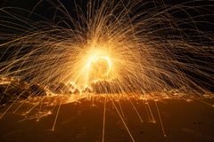 Swing fire Swirl steel wool light photography over the stone with reflex in the water long exposure speed motion style.  royalty free stock photography