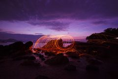 Swing fire Swirl steel wool light photography over the stone wit. H reflex in the water Beautiful light in the sunrise or sunset time, long exposure speed motion royalty free stock images