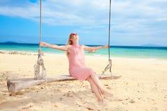 Swing fun. Beautiful woman has fun on the swing Stock Photo