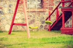 Swing in garden playground, brick wall background Stock Photo