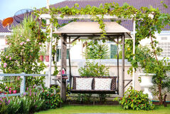 Swing in the garden. The vintage swing in beautiful garden Stock Images