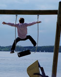 Swing + jump. Boy jumping from a swing at a fjord Stock Photos