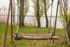 Swing at lake. Original makeshift swing on the lake in spring Stock Images