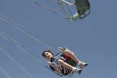 Swing Low. A young boy on an amusement park ride Royalty Free Stock Image