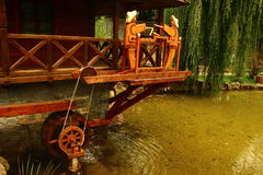 Swing mechanism of water. Wooden rocking mechanism of water from the two men, and the turbine shaft Royalty Free Stock Photos