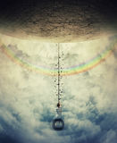 Swing over the rainbow. Young boy suspend on a tire swing in the clouds over the rainbow, avoiding the gravitational force. Having fun and freedom concept Royalty Free Stock Images
