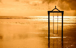 a swing over the sea at sunset in bali,indonesia Royalty Free Stock Image