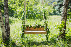 Swing overgrown with flowers Royalty Free Stock Image