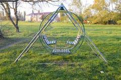 Swing på lekplatsen 2 children playground Gungor och en glidbana som glider Arkivfoton