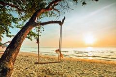 Swing på solnedgång på stranden Royaltyfria Bilder