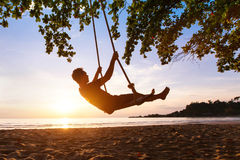 Swing on paradise tropical beach at sunset Stock Photos