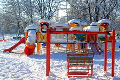 Swing and playground covered with snow Stock Image