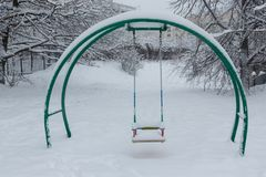 Swing at the playground covered with snow. After a heavy snowfall Stock Image