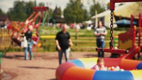 Swing on playground focus in. Woman sway kids on swing, children play. Summer day stock footage