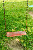 Swing. Red swing in the garden Royalty Free Stock Photo