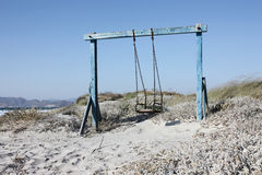 Swing at seaside with sand. Derelict blue swing in sand Stock Photography