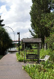 Swing Seat and Broadwalk. Singapore - August 2016 Swing seat along the broadwalk at the Gardens with the Singapore Flyer in the background royalty free stock images