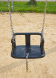 Swing seat on chains. Swing set seat hanging on metal chains at a playground Royalty Free Stock Photo