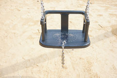 Swing seat on chains. Swing set seat hanging on metal chains at a playground Royalty Free Stock Images