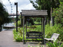Swing Seat. Singapore - August 2016 Swing seat along the broadwalk at the Gardens by the Bay with the Singapore Flyer in the background royalty free stock photo