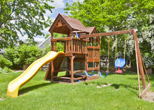 Swing Set. Back Yard Wooden Swing Set on Green Lawn royalty free stock images