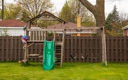 Swing set in backyard during spring season. With lush grassy lawn stock image