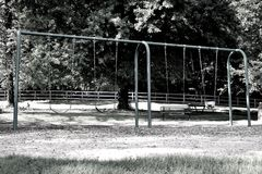 Swing Set in the Park. A simple yet extraordinary digital art photo of a child favorite. Print, share and reminisce the sweet memories of the swing set stock photography