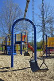 Swing Set In Playground. This swing set is located a town called, Ajax Ontario.  You can see the thick chain on the swings.  And, in the background you can see Royalty Free Stock Photography