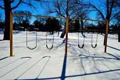 Swing Set Shadows Snow. A yellow swing set at a park casting cool shadows in the freshly fallen snow Royalty Free Stock Photo