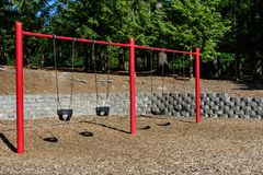 Swing set on a sunny day in a park playground, four classic black rubber swings with red posts. Wood chips below and woodland behind stock image